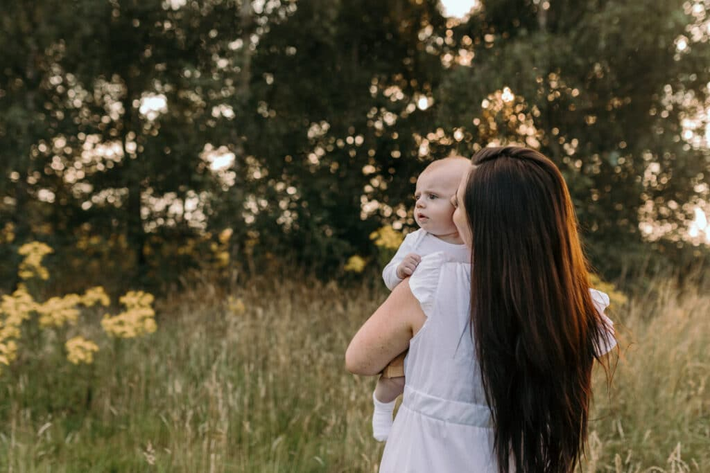 Mum is standing back to the camera and her little boy is looking away. Lovely sunset photosession. Family photography in Hampshire. Ewa Jones Photography