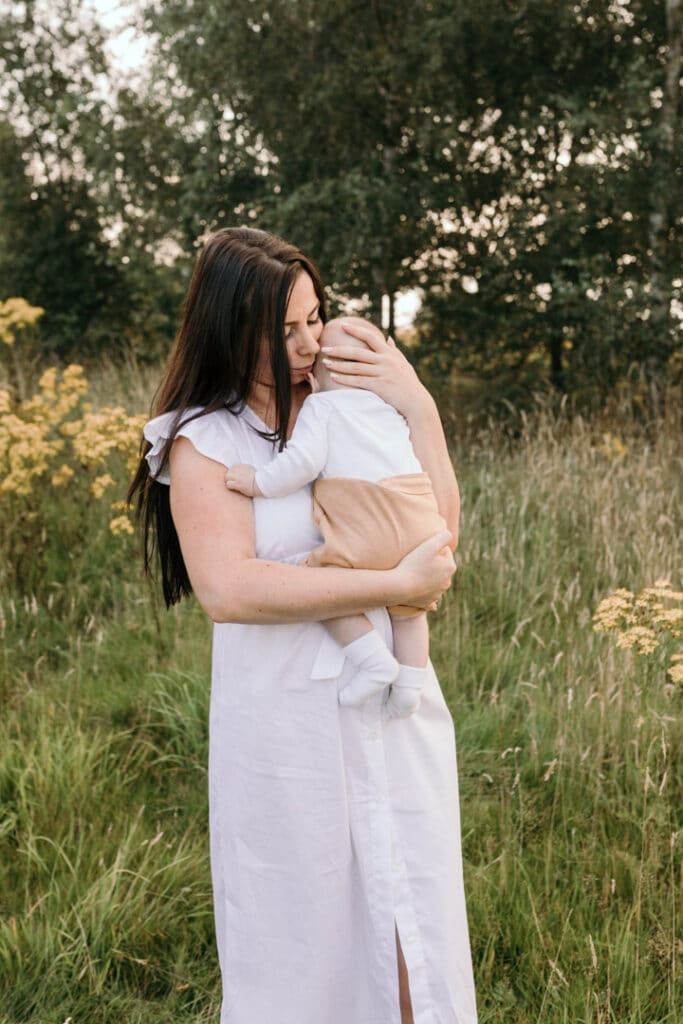 Mum is holding close her little baby boy and standing in the field of flowers. Sunset photo session. Mum is lifting up her little baby boy and he is looking at the camera and smiling. Sunset photo session in Basingstoke. Family photographer in Hampshire. Ewa Jones Photography