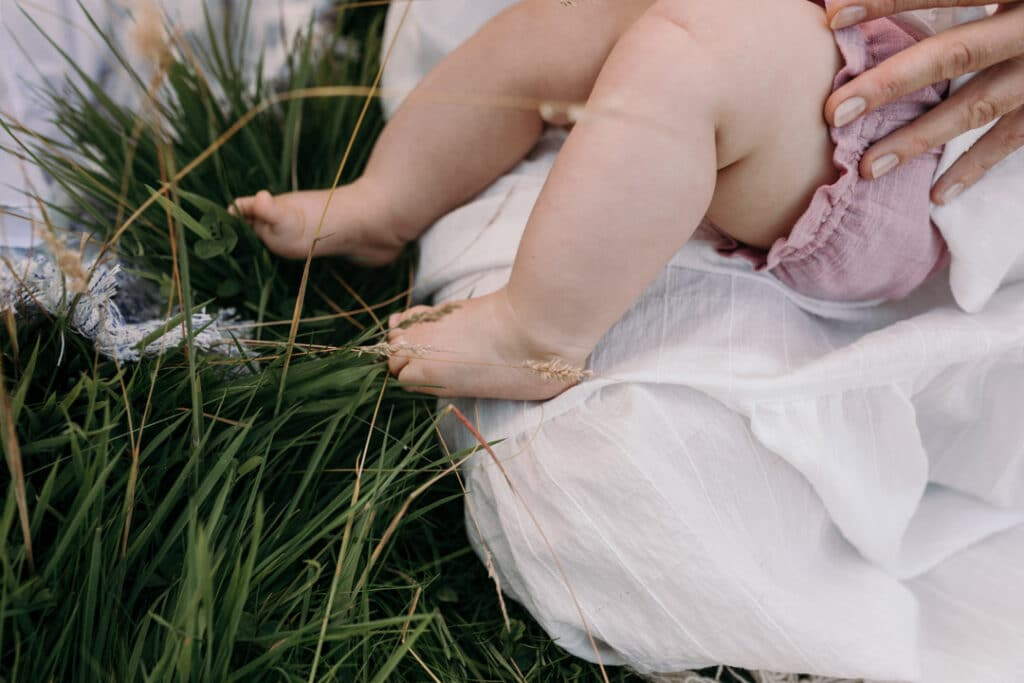 Close up detail of baby girl feet. the feet are touching the grass and the little girl is laying on mummy and breastfeeding. Family photography in Hampshire, Ewa Jones Photography