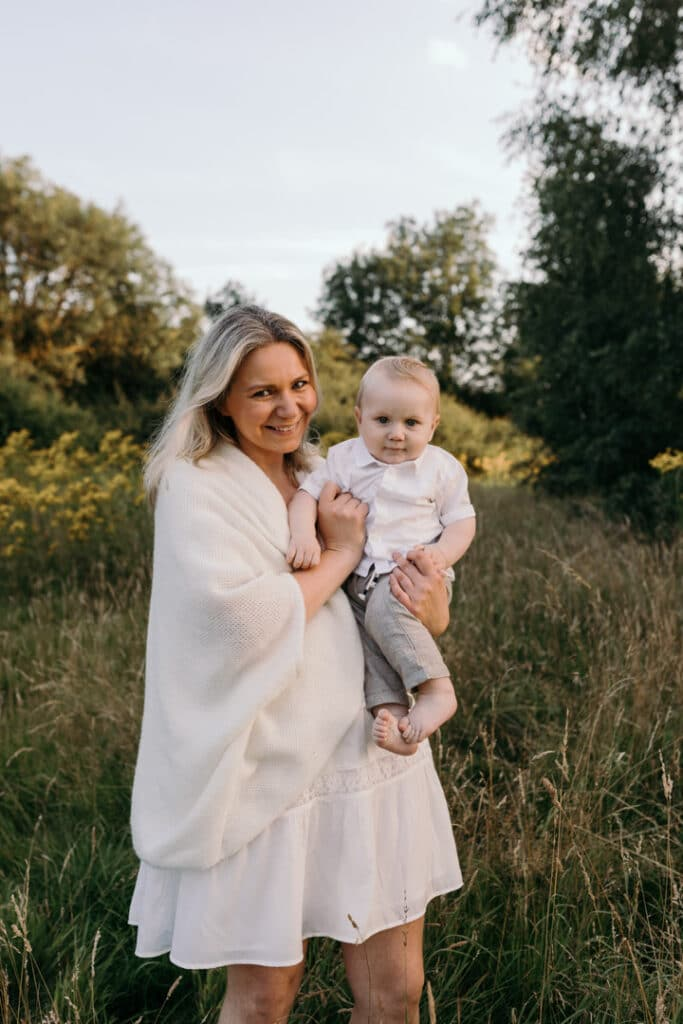 Mum is holding her baby boy and smiling. Mum is wearing lovely white dress and boy is wearing white shirt and grey trousers. Family photography in Basingstoke, Hampshire. Ewa Jones Photography
