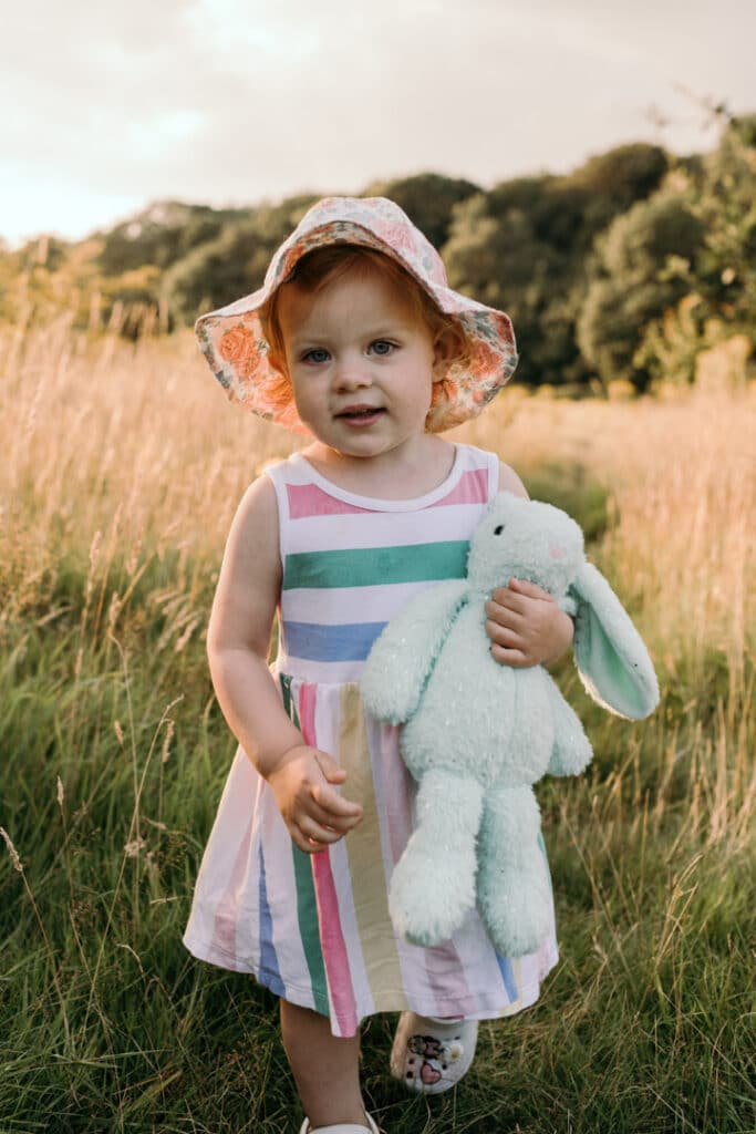 Little girl is walking in the field of long grass. She is wearing lovely stripy dress, flower hat and is holding her bunny. Family photographer in Hampshire. Ewa Jones Photography
