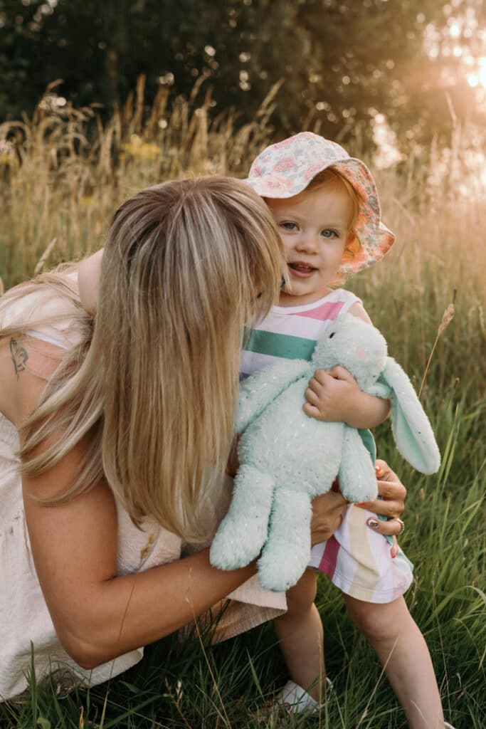 Mum is kissing her girl in her cheek. The sun is shining and making the gold sunset. Little girl is walking in the field of long grass. She is wearing lovely stripy dress, flower hat and is holding her bunny. Family photographer in Hampshire. Ewa Jones Photography