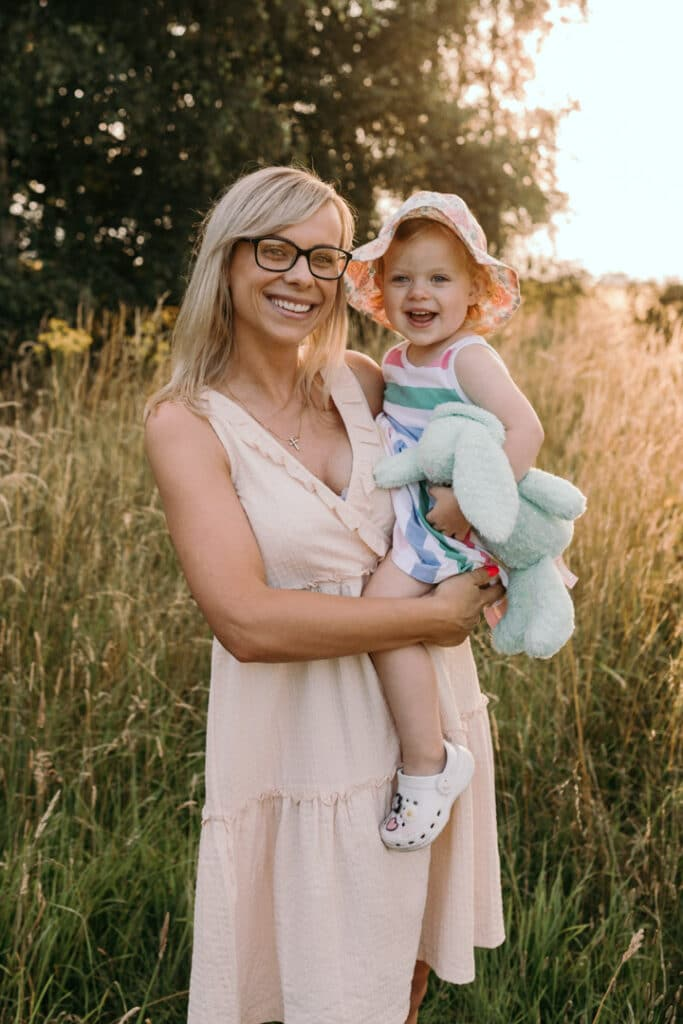 Mum and her girl are standing in the long grass. Mummy and me photo session in Hampshire. Ewa Jones Photography