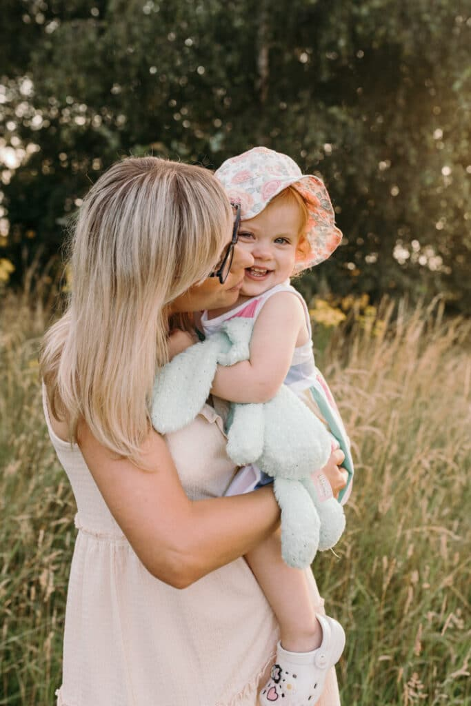 Cuddles with mummy. Little girl is cuddling to her mum and smiling to the camera. She is holding her rabbit toy and wearing stripy dress and flower hat. Family photography in Hampshire. Ewa Jones Photography