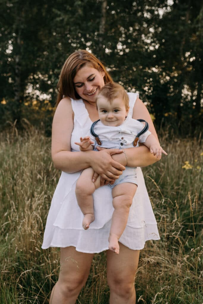 Mum is holding her little boy and looking down on him. Her boy is smiling at the camera. Family photo shoot. Family photographer in Hampshire. Ewa Jones Photography