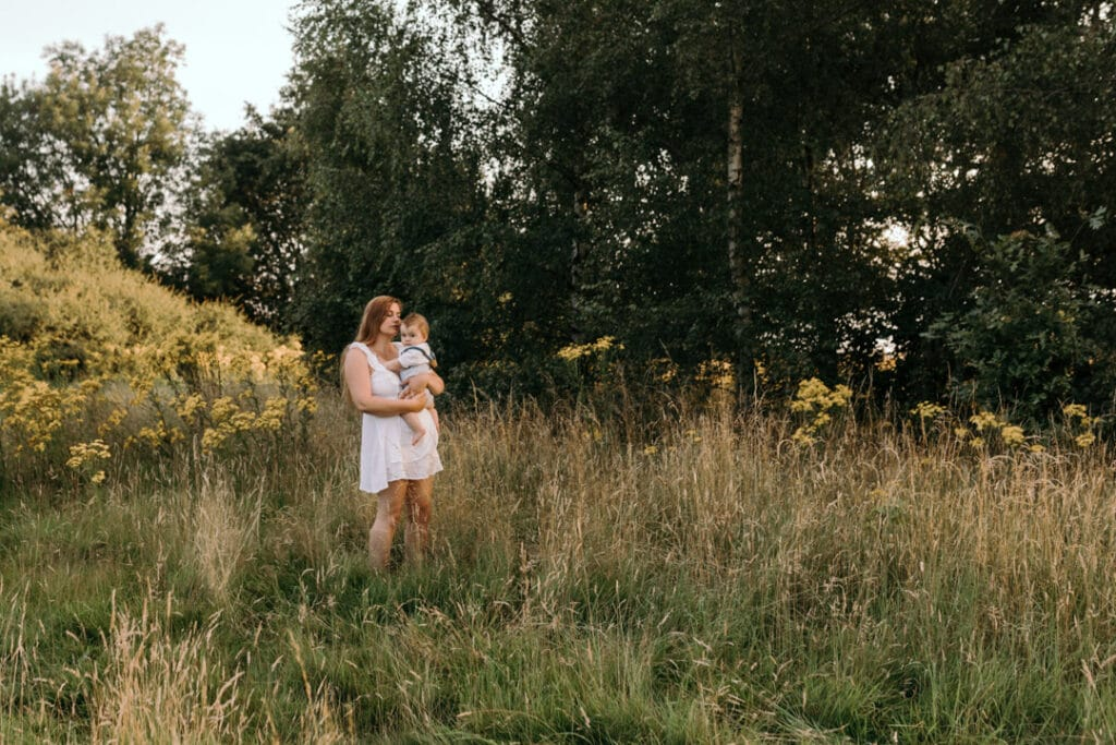 Mum is standing in the field of wild flowers and looking down at her boy. Gorgeous photo shoot in the field. Family photography in Hampshire. Ewa Jones Photography