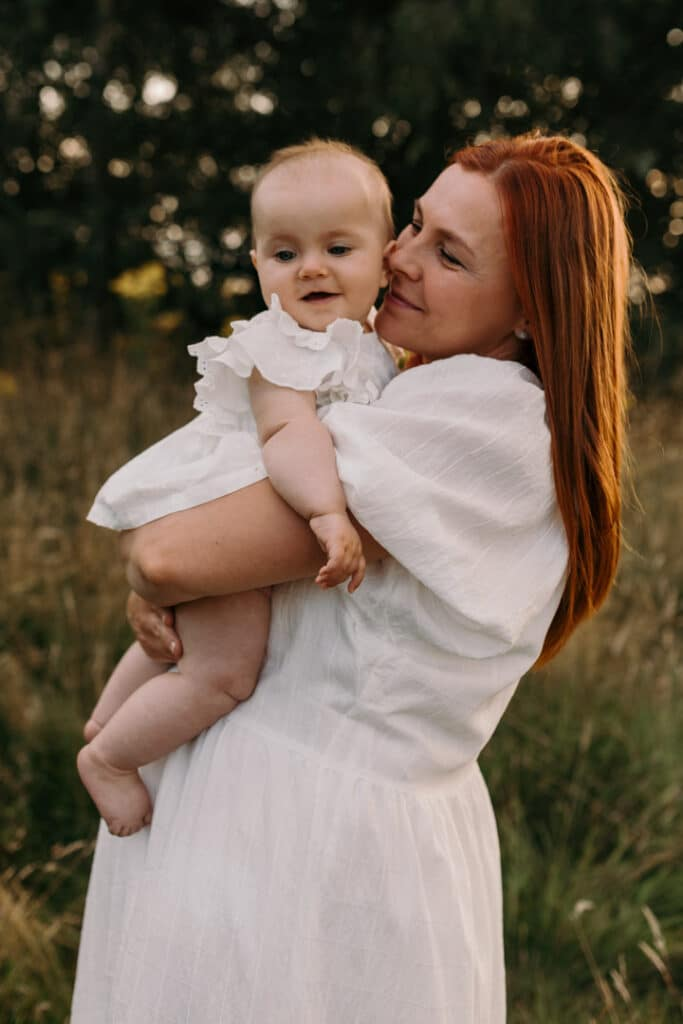 Mum is wearing lovely white dress and looking at her baby girl. Baby girl is also wearing lovely white top and smiling. Family photography in Basingstoke, Hampshire. Ewa Jones Photography