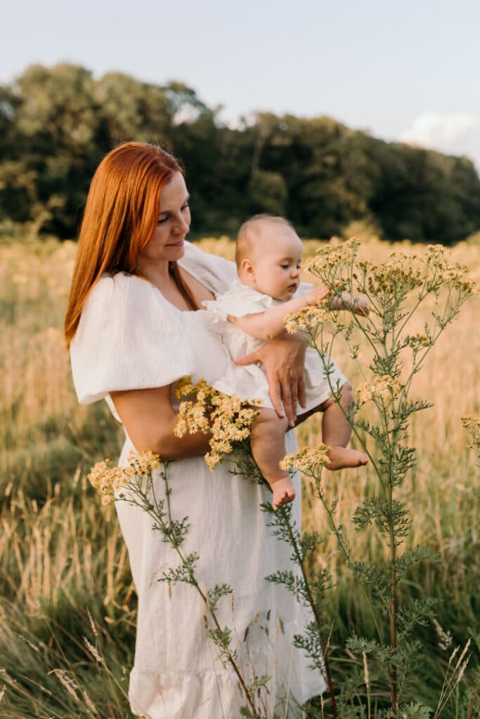Mum is holding her baby girl and baby girl is touching wild flowers on the field. Lovely sun is shining on mmmy's back. Family photographer in Hampshire. Ewa Jones Photography
