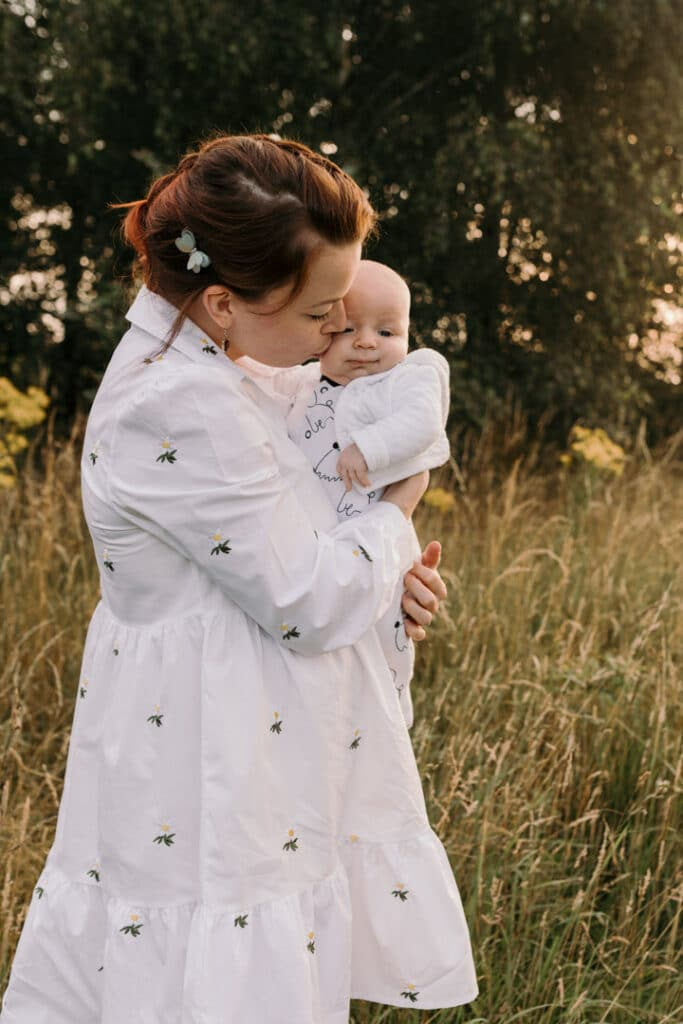 Mum is kissing her baby boy on his cheek. Mum is wearing lovely white dress with white daisies. Sunset photo shoot in the wild flower field. Family photography in Basingstoke, Hampshire. Ewa Jones Photography
