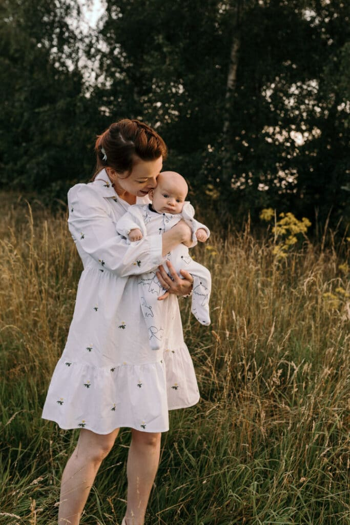 Mum is cuddling her baby boy. Mum is wearing lovely white dress with white daisies. Sunset photo shoot in the wild flower field. Family photography in Basingstoke, Hampshire. Ewa Jones Photography