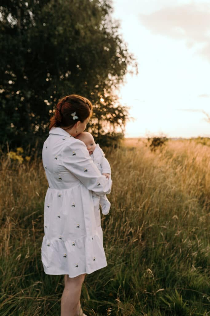 Mum is cuddling her baby boy and looking at the sunset. Mum is kissing her baby boy on his cheek. Mum is wearing lovely white dress with white daisies. Sunset photo shoot in the wild flower field. Family photography in Basingstoke, Hampshire. Ewa Jones Photography