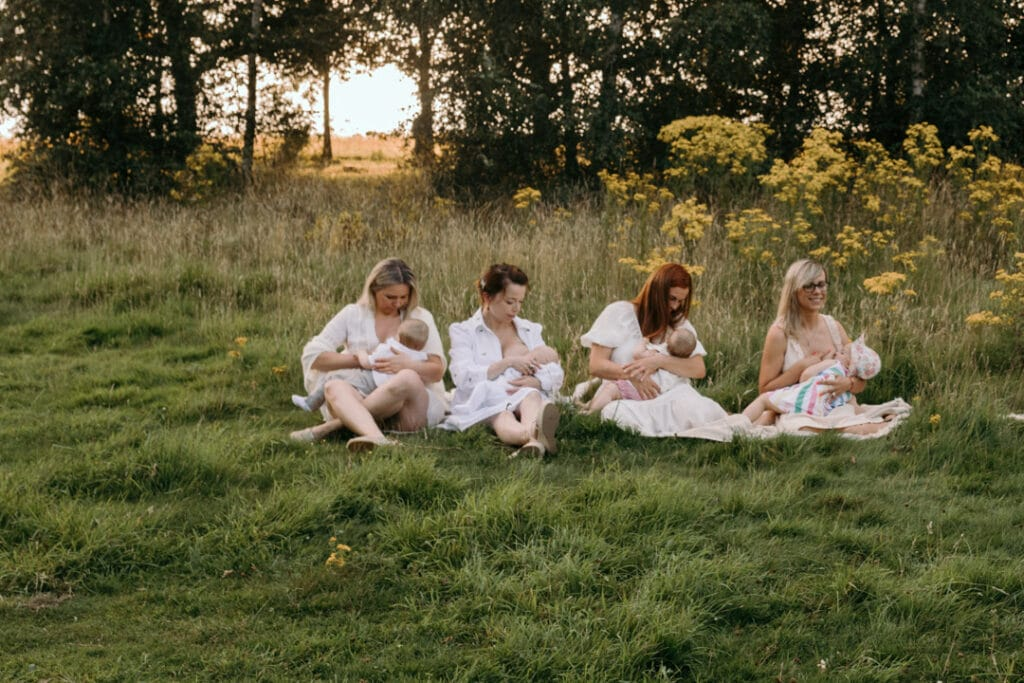 four mums are sitting on the blanket and breastfeeding their babies. There is a gorgeous field full of wild flowers and the sun is shining through the trees. Group breastfeeding photo session in Basingstoke, Hampshire. Ewa Jones Photography