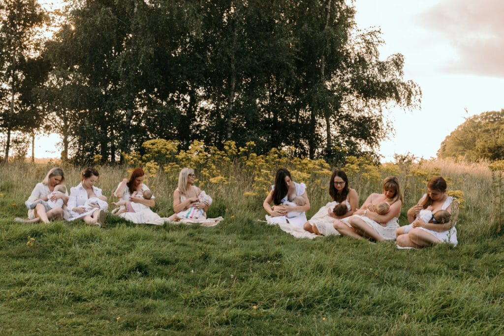mums are sitting on the blanket and breastfeeding their babies. There is a gorgeous field full of wild flowers and the sun is shining through the trees. Group breastfeeding photo session in Basingstoke, Hampshire. Ewa Jones Photography