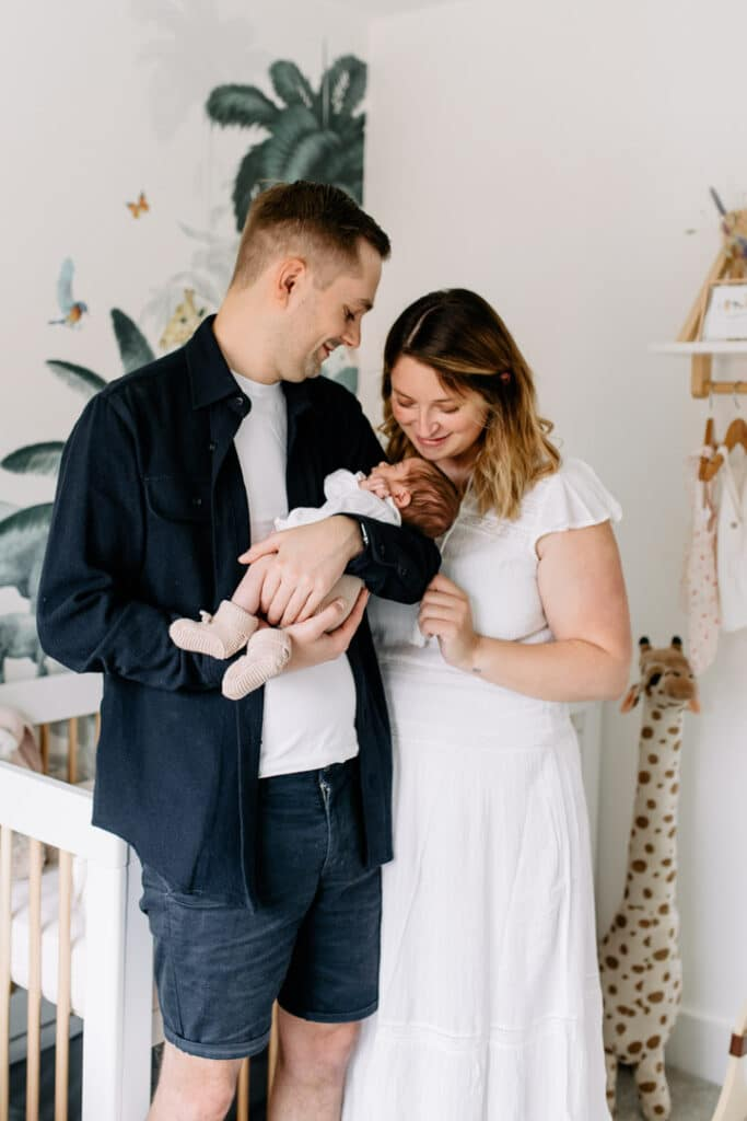 Mum and dad are standing in a lovely safari theme nursery and holding their newborn baby girl in their arms. Newborn photographer in Basingstoke, Ewa Jones Photography
