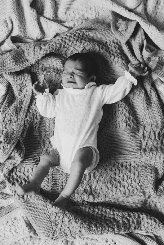 Baby girl is laying on blankets and raising her hands up. Newborn baby photoshoot in Basingstoke, Hampshire. Ewa Jones photography
