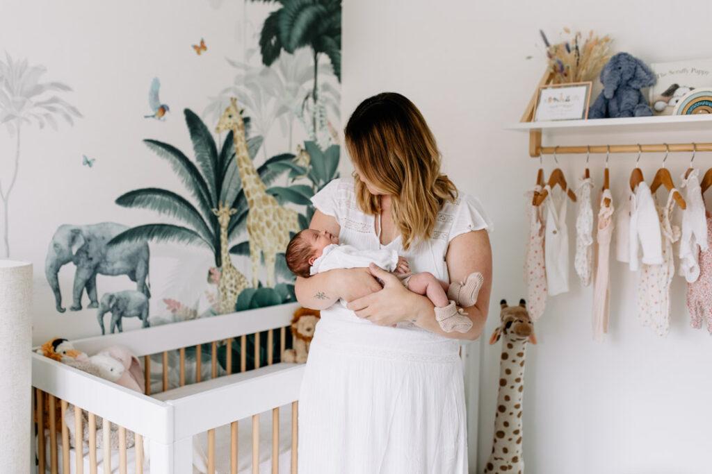 Mum is holding her newborn baby girl. Lovely natural light is coming through the windows. Newborn photographer in Hampshire. Ewa Jones Photography