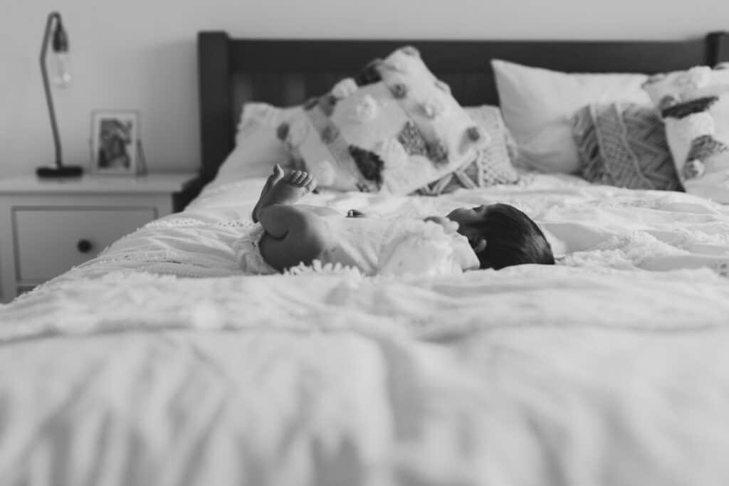 Newborn baby girl is laying on the bed. Black and white photograph. Newborn photoshoot in Basingstoke, Hampshire. Ewa Jones Photography