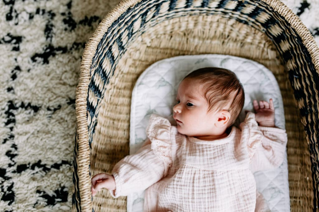 Newborn baby girl is laying inside her moses basket and looking up. In home newborn photography in Hampshire. Ewa Jones Photography