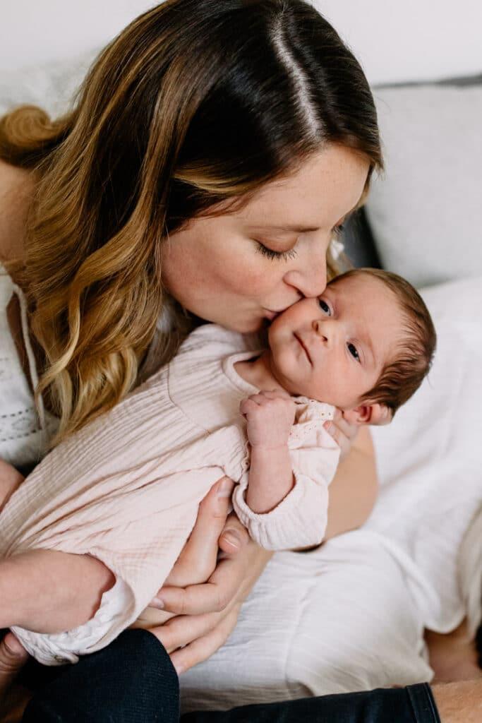 Mum is kissing her newborn baby girl on her cheek. Newborn baby is wearing lovely cream baby grow. Newborn photographer in Hampshire. Ewa Jones Photography