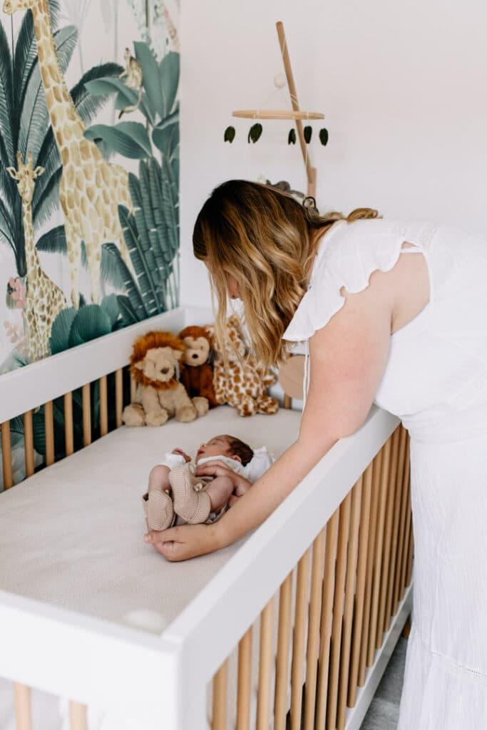 Newborn baby girl is laying in her cot in her beautiful jungle theme nursery. Newborn photo shoot in Hampshire. Ewa Jones Photography