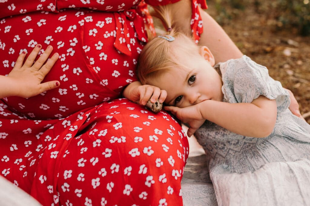 Little girl is resting her head on mummy's leg. she is looking at the camera. Her older sister is touching baby bump. maternity photo shoot in Hampshire. Ewa Jones Photography