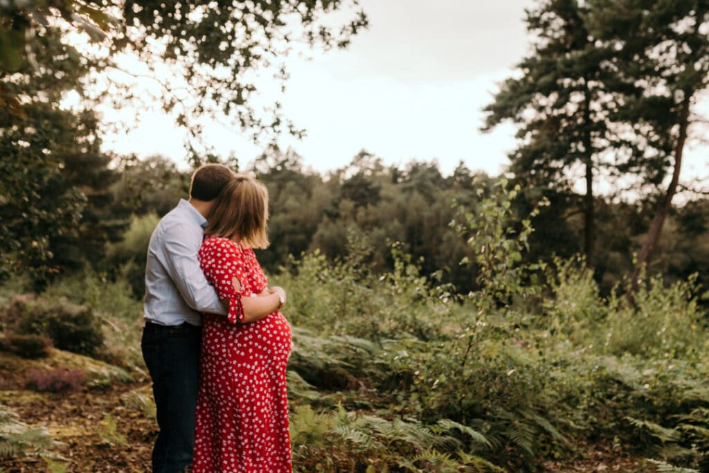 expecting mum and dad are cuddling to each other and looking away from the camera. maternity photoshoot in Hampshire. Ewa Jones Photography