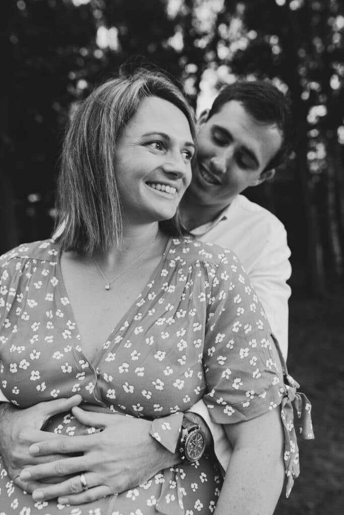 Black and white photograph of expecting mum and her husband. Her husband is looking at her lovingly. Lovely maternity photography in Hampshire. Ewa Jones Photography