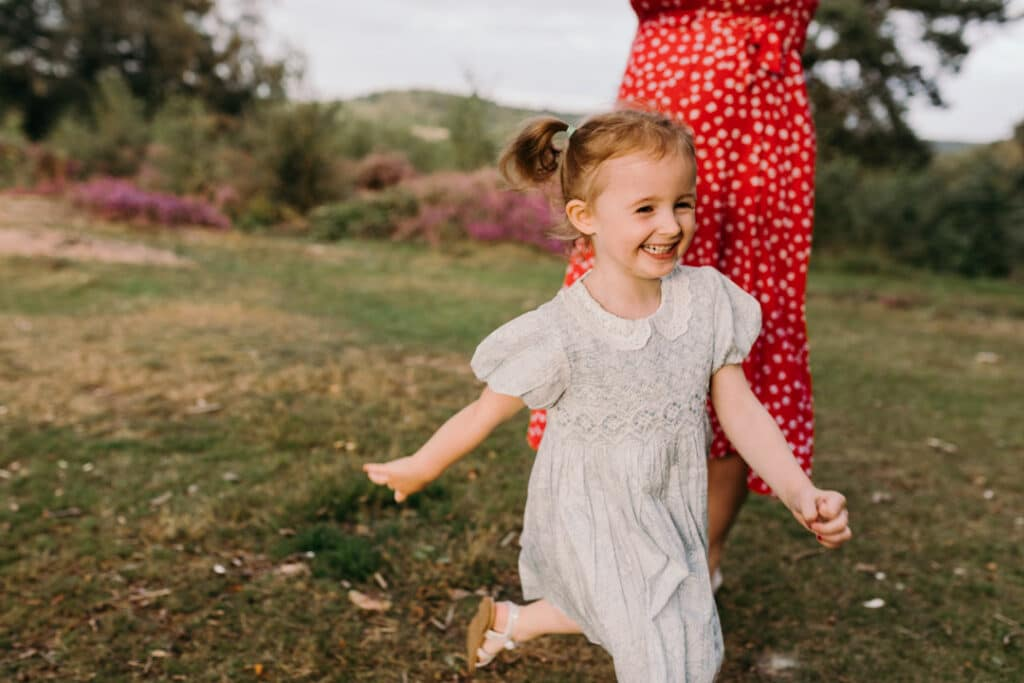 little girl is running and laughing. family photographer in Basingstoke, Hampshire. Ewa Jones Photography