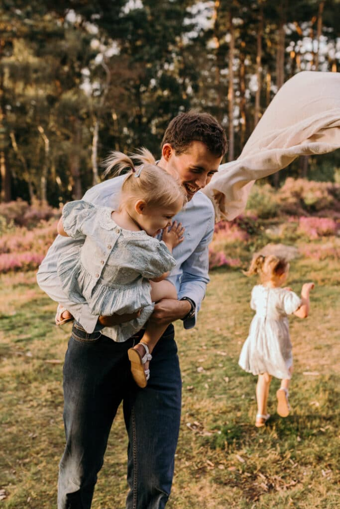 dad is running with his daughter and laughing. lovely family photograph during family photo session. family photographer in Hampshire. Ewa Jones Photography