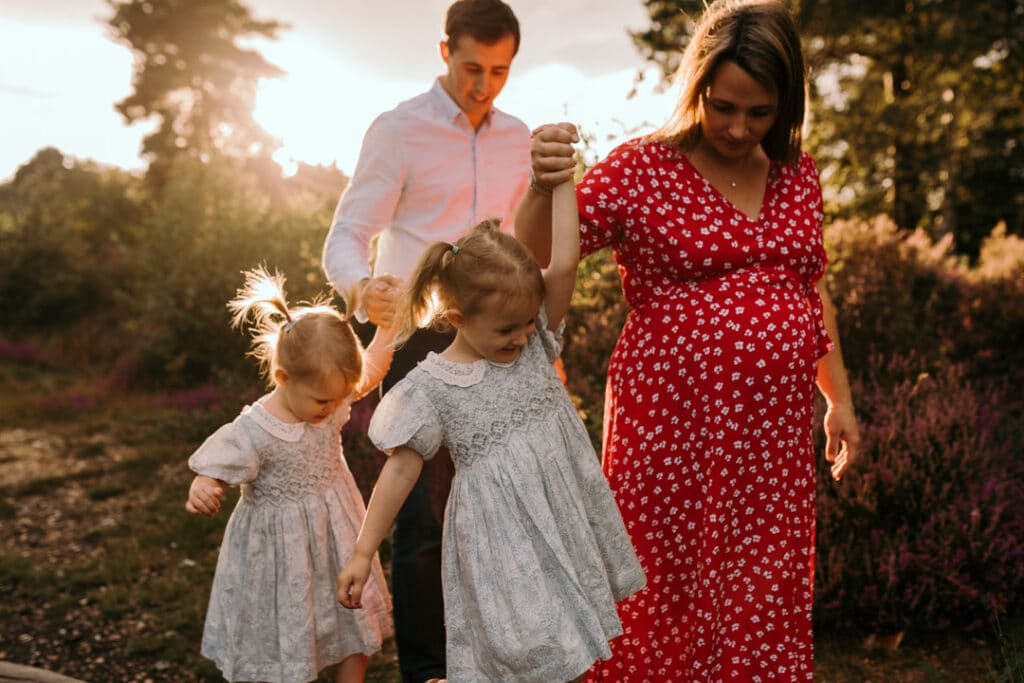 mum and dad are holding hands with their daughters and the girls are walking on the wooden log. lifestyle family photographer in Hampshire. Ewa Jones Photography