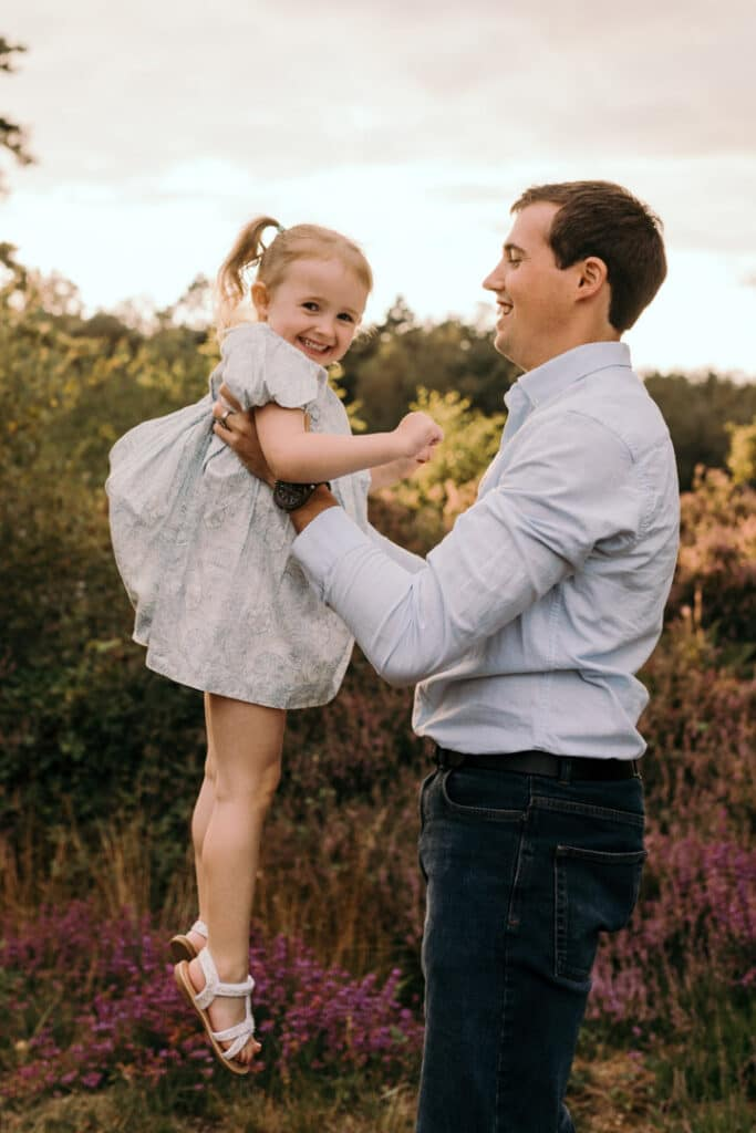 dad is lifting up his daughter in the air and they are both laughing. family photographer in Basingstoke, Hampshire. Ewa Jones Photography