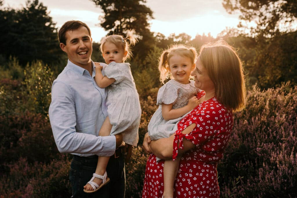family of four is laughing and mum is looking at her husband and younger daughter and the older daughter is looking at the camera. Golden hour maternity photography in Hampshire. Ewa Jones Photography