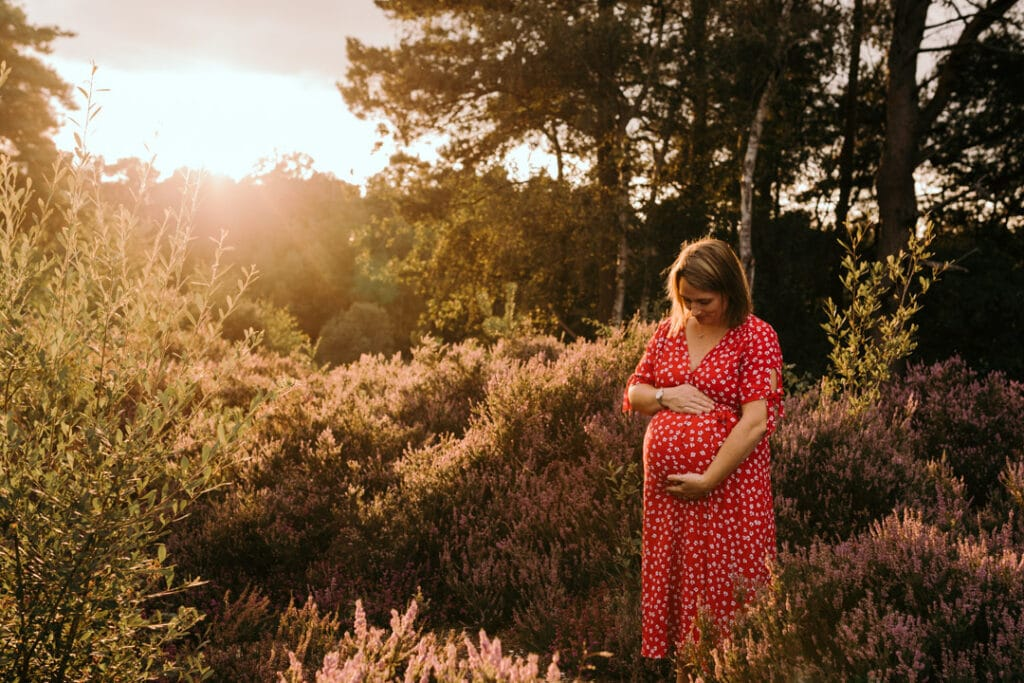 Expecting mum is looking down at her baby bump and holding her bump. It's a lovely summer evening and sun is shining behind mum. Maternity photoshoot in Hampshire. Ewa Jones Photography