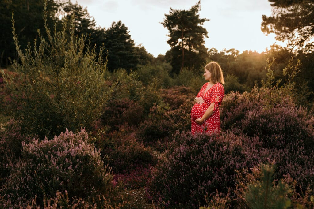 Expecting mum is looking away and holding her baby bump. it's a lovely summer evening and sun is shining behind expecting mum. maternity photographer in Basingstoke, Hampshire. Ewa Jones Photography