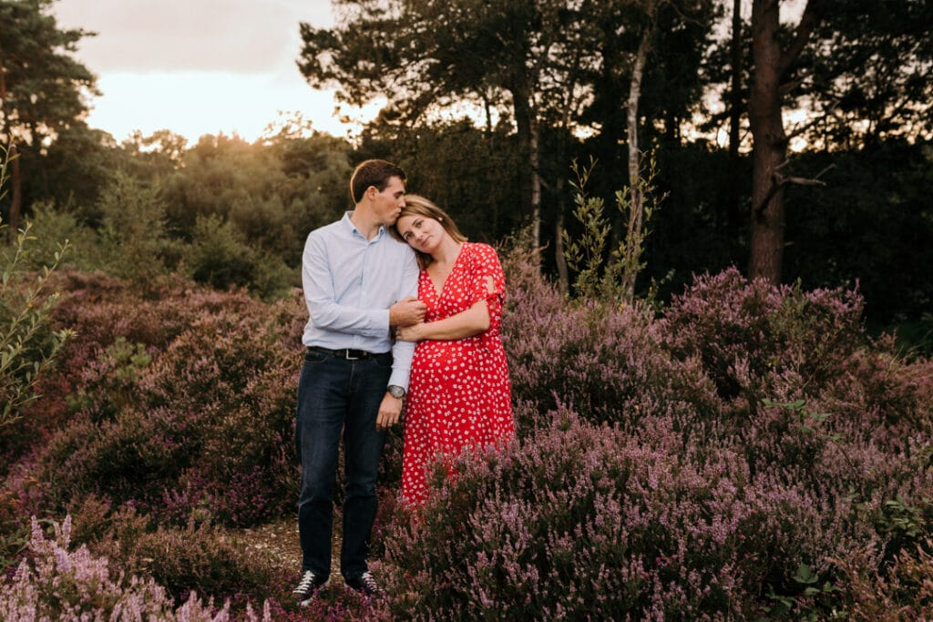 expecting parents are standing in the fields of lovely purple flowers. Pregnant mum is wearing a red dress with white flowers. dad is kissing mum on top of her head. maternity photo session in Hampshire. Ewa Jones Photography