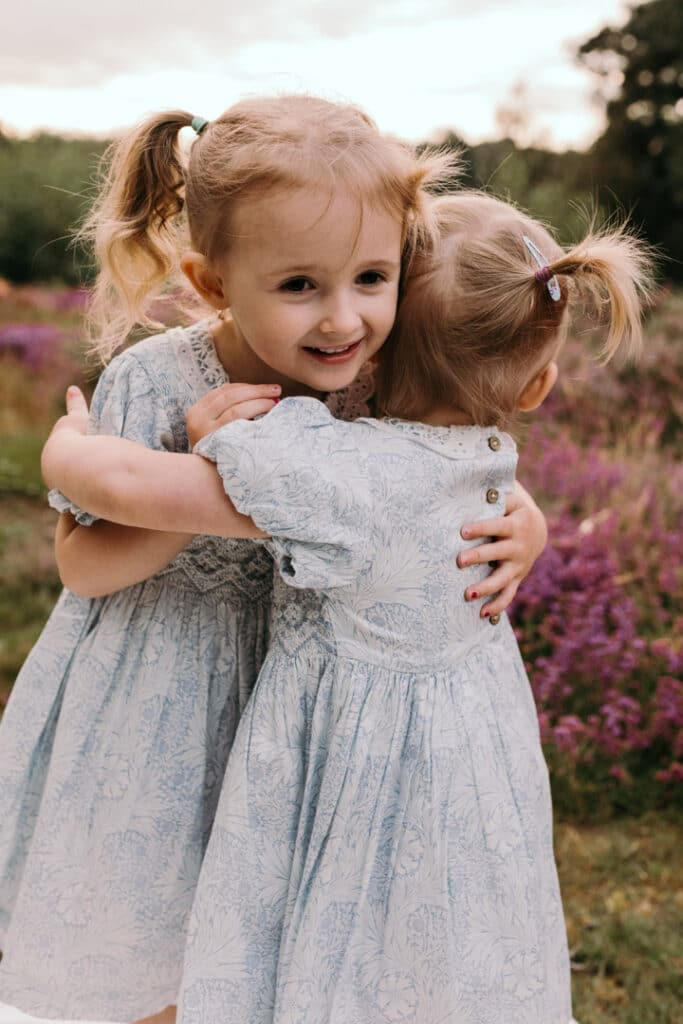 two lovely sisters and giving each other a cuddle. Lovely family photo session during sunset. Family photographer in Hampshire. Ewa Jones Photography