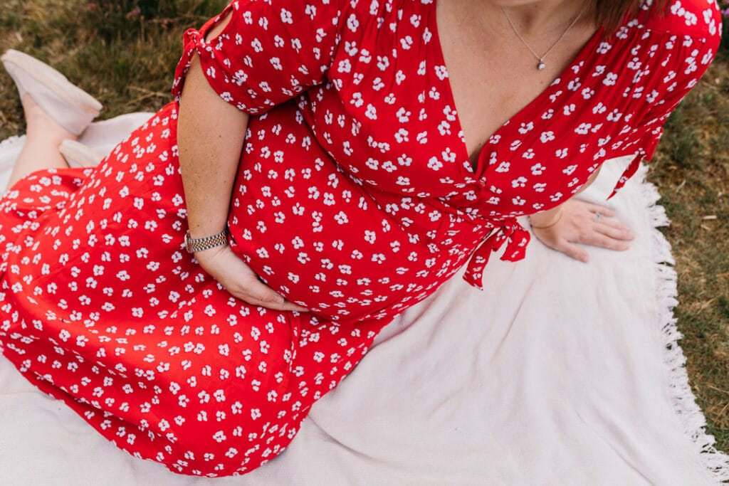 close up picture of expecting mum bump. Mum is wearing lovely red dress with white flowers. maternity photography in Basingstoke, Hampshire. Ewa Jones Photography