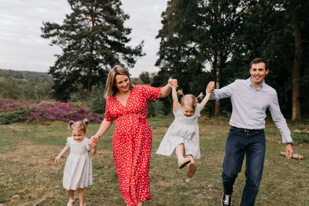Family of four are walking towards the camera and mum and dad are swinging their younger daughter. lovely family photo session in Hampshire. Family photographer in Hampshire. Ewa Jones Photography