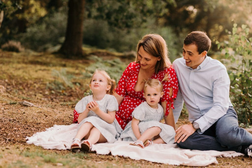 Family of four are sitting on the blanket. its a lovely summer evening and photo session is during golden hour. Family photographer in Basingstoke, Hampshire. Ewa Jones Photography