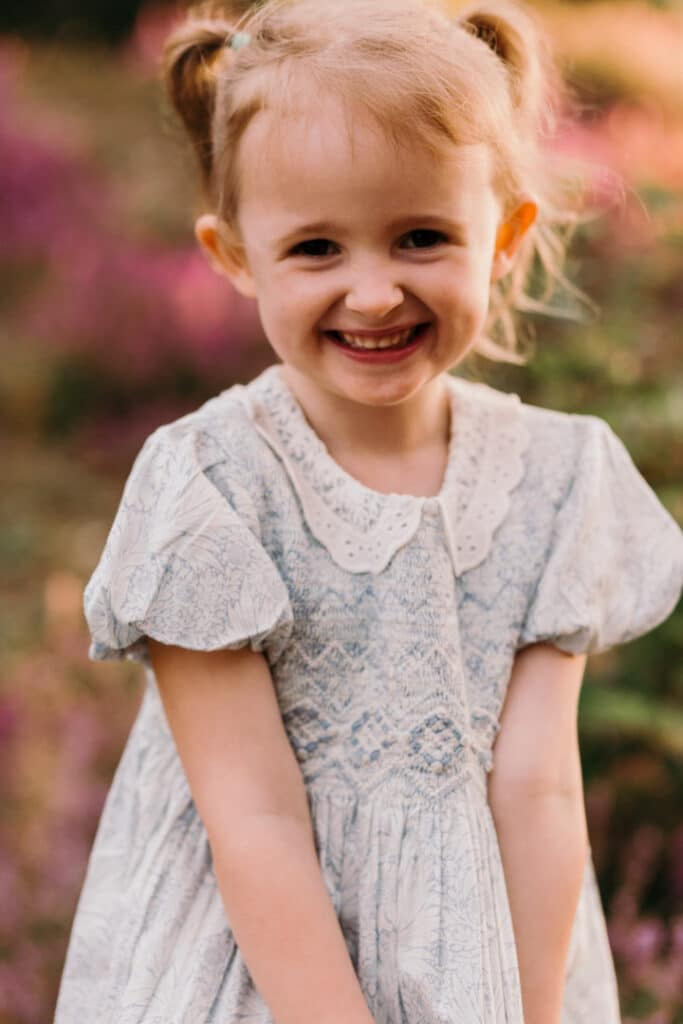 Little girl is wearing a lovely blue and white flower dress. she has two ponytails and looking at the camera. Lovely sunset and golden hour photo session. Family photography in Hampshire, Ewa Jones Photography