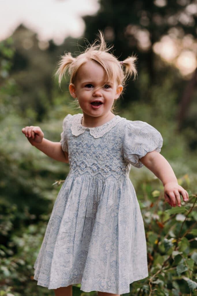 Little girl is wearing a lovely blue and white flower dress. she has two ponytails and looking at her parents. Lovely sunset and golden hour photo session. Family photography in Hampshire, Ewa Jones Photography