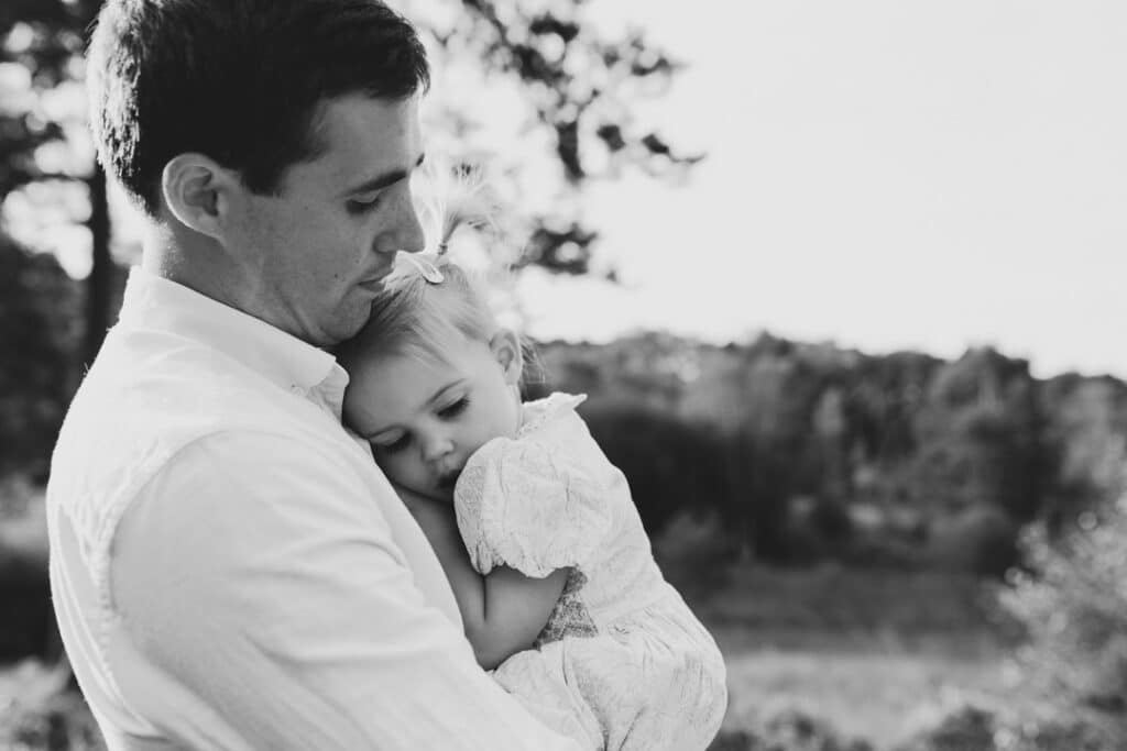 Little girl is cuddling up to her dad. Black and white photograph. family photographer in Basingstoke, Hampshire. Ewa Jones Photography