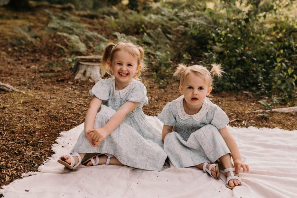 two sisters are sitting on the blanket and looking at the camera. they bothe are wearing the same blue and white dresses and two ponytails. lovely family photography in Hook, Hampshire. Ewa Jones Photography