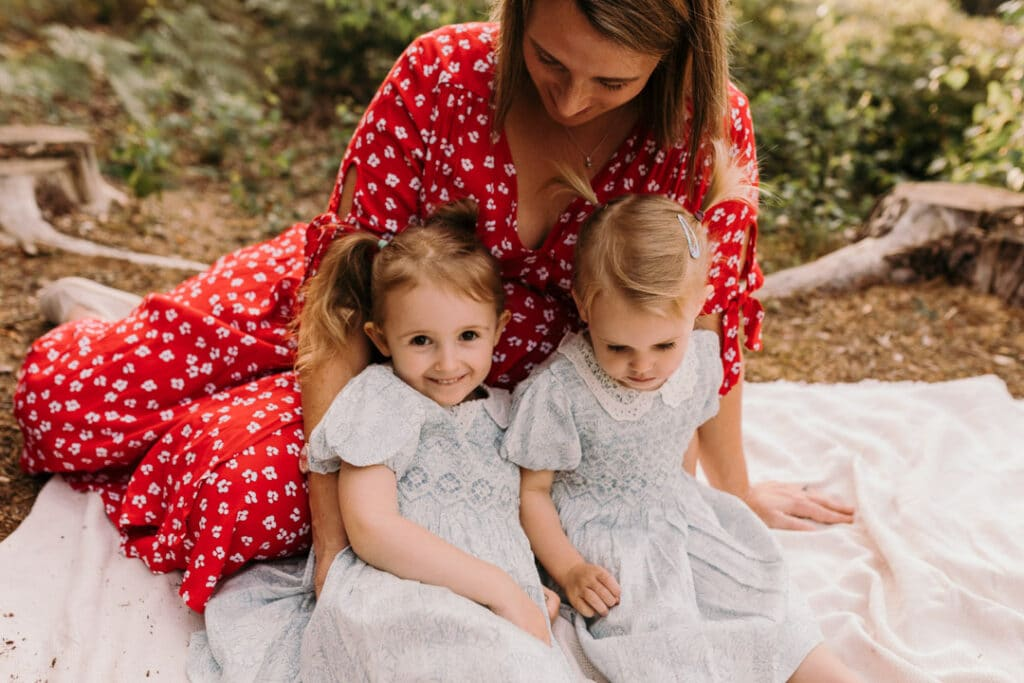 expecting mum and her two daughters are sitting on the blanket. maternity photo session in Hampshire. Ewa Jones Photography