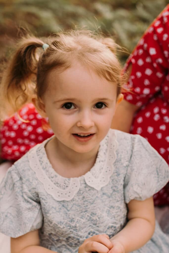 Little girl is looking at the camera. she is wearing lovely blue dress and has two ponytails. Lovely family photo sessions in Hampshire. Ewa Jones Photography